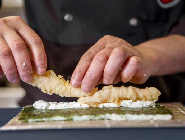 Maestro del sushi colocandolo sobre el plato de una forma muy curiosa